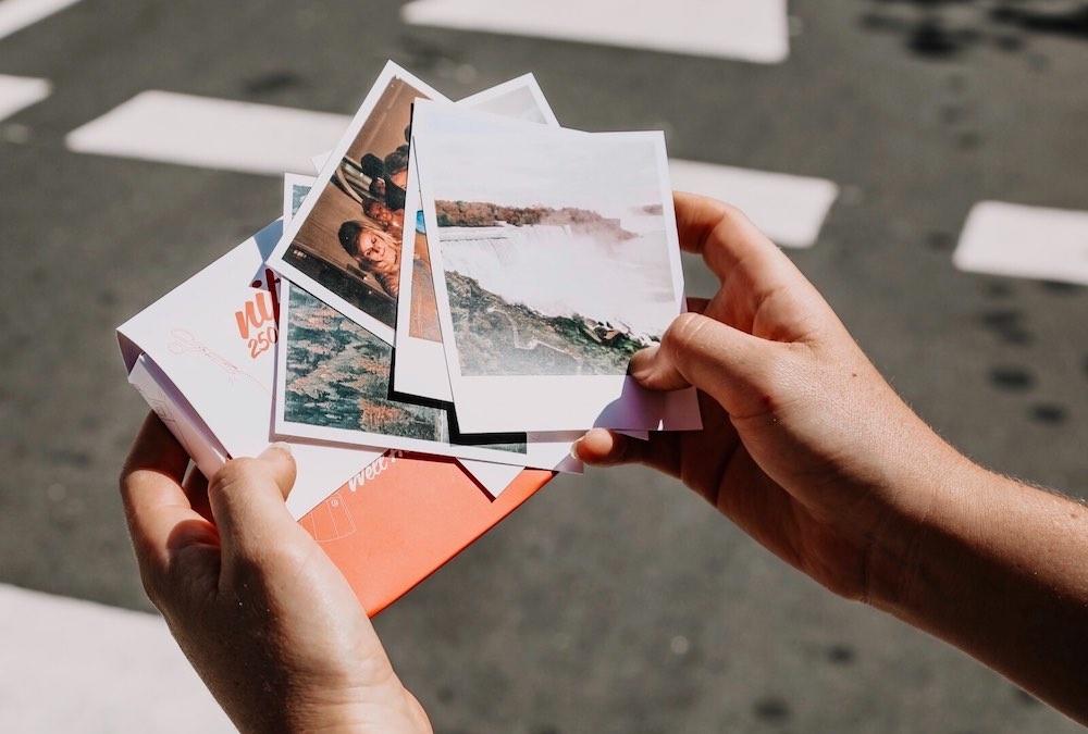 polaroid prints in hand outside